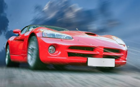 red sports powerful car on stone blocks against  sky