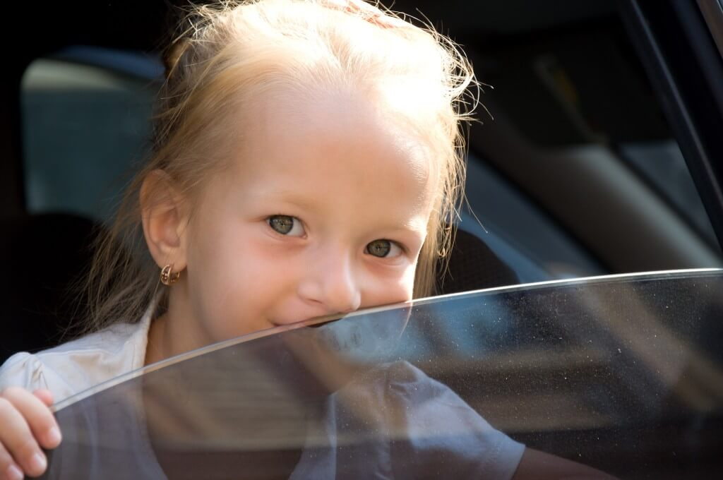 child looking out tinted car window