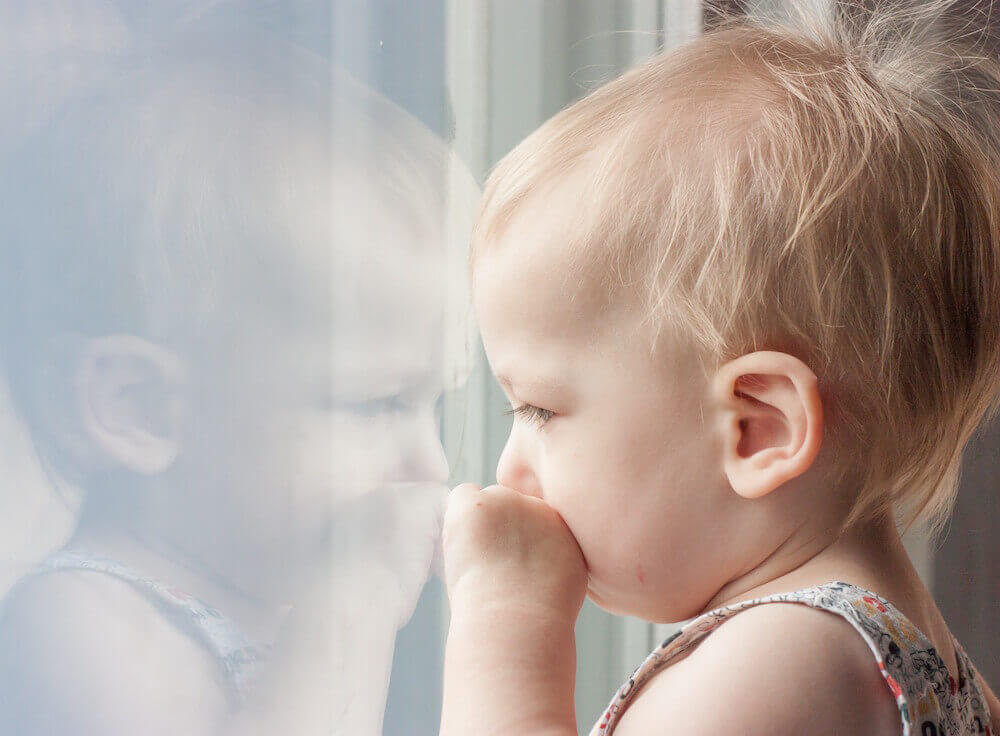 child gazing out home window