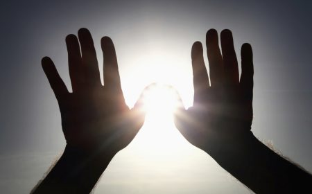 Silhouette of human hands held up against the sun, shielding against sun flare.