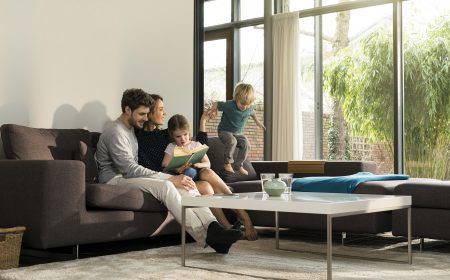 Family on sofa at home reading book with boy jumping